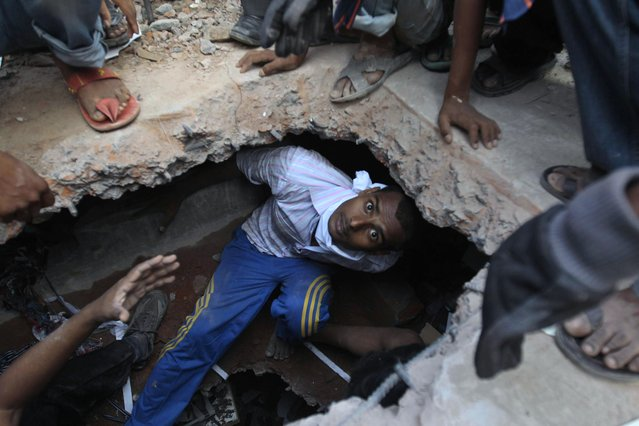 A Bangladeshi rescuer looking for survivors emerges from beneath a concrete slab of a building that collapsed Wednesday in Savar, near Dhaka, Bangladesh, Thursday, April 25, 2013. By Thursday, the death toll reached at least 194 people as rescuers continued to search for injured and missing, after a huge section of an eight-story building that housed several garment factories splintered into a pile of concrete on Wednesday. (Photo by A. M. Ahad/AP Photo)