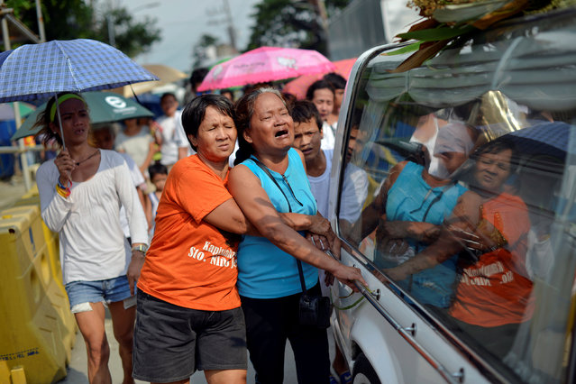 Friends and relatives of two cousins killed by masked gunmen mourn as they follow they coffins to a cemetery in Manila, Philippines October 11, 2016. (Photo by Ezra Acayan/Reuters)