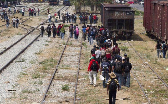 Migrants walk along the rail tracks after getting off a train during their journey toward the US-Mexico border in Ixtepec, southern Mexico, April 29, 2013. Migrants crossing Mexico to get to the U.S. have increasingly become targets of criminal gangs who kidnap them to obtain ransom money. (Photo by Eduardo Verdugo/AP Photo)