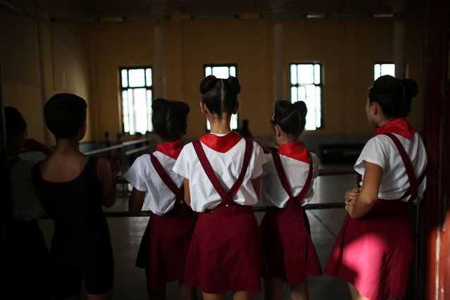 Students at the Cuba's National Ballet School (ENB) watch a class from outside the classroom in Havana, Cuba, October 12, 2016. (Photo by Alexandre Meneghini/Reuters)