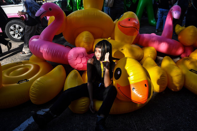 A pro-democracy protester gives the three-finger salute as she poses on an inflatable duck during an anti-government rally outside the headquarters of the Siam Commercial Bank in Bangkok on November 25, 2020. (Photo by Lillian Suwanrumpha/AFP Photo)