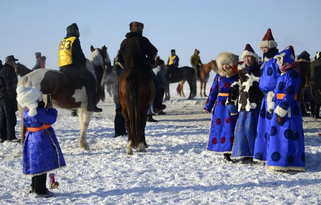 People pose for photographs in traditional Mongolian costumes on a grassland covered in snow during a winter Naadam event in Hulun Buir, north China's Inner Mongolia Autonomous Region, December 23, 2014. (Photo by Reuters/Stringer)