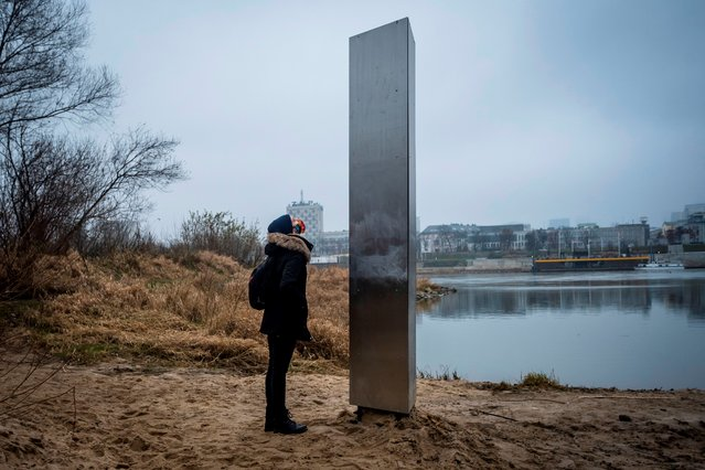 A woman looks on December 10, 2020 at a metal monolith that has popped up on a riverbank of the Vistula in the Polish capital Warsaw, the latest in a string of similar objects that have recently appeared in Europe and the US. Similar-looking objects were found in the United States, Romania and Britain. (Photo by Wojtek Radwanski/AFP Photo)