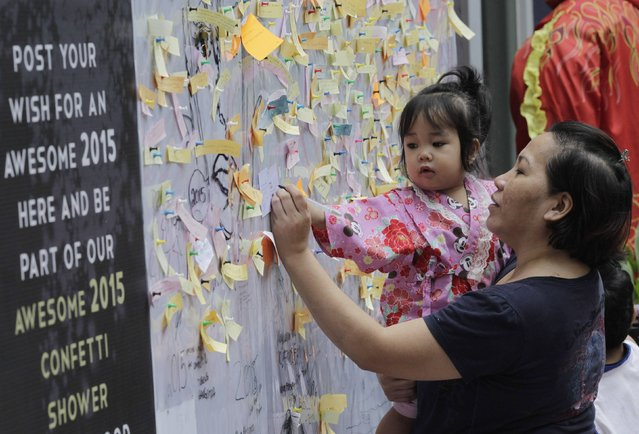 A woman writes her New Year wishes on a wishing wall display at a mall in Quezon city, metro Manila December 31, 2014. (Photo by Romeo Ranoco/Reuters)