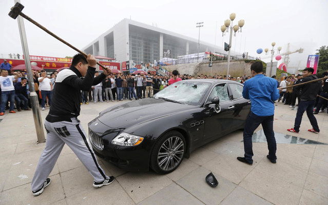 A man in China hired three people to destroy his Maserati – worth almost half a million dollars – because he was angry with the car dealer last Tuesday, May 14, 2013. The owner, identified only as Wang, paid the men to trash his $423,000 Maserati Quattroporte, worth N66.8million naira at the Qingdao International Auto Show. According to Car News China, Wang claimed the dealer had replaced faulty parts in his vehicle with used parts; he also accused both the dealer and an insurance company of fraud. (Photo by Reuters/Stringer)