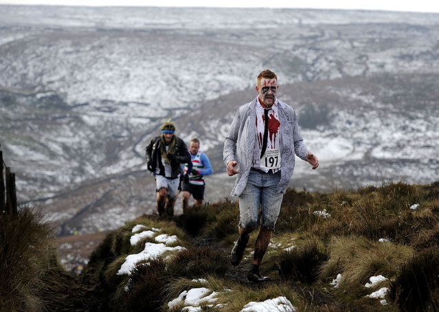 Costumed runners cross the Pennine hills near Haworth in northern England in the annual Auld Lang Syne 9.6-kilometer race, which includes a costume contest and free beer for all finishers, on December 31, 2014. (Photo by John Giles/AP Photo)