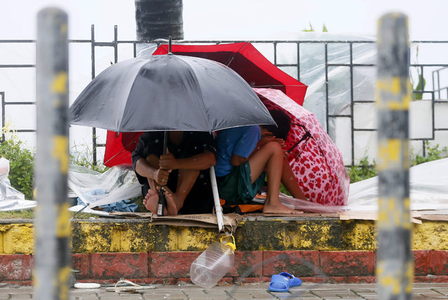 Residents huddle together under their umbrellas as strong winds and slight rain are brought by Typhoon Koppu Sunday, October 18, 2015 in Manila, Philippines. (Photo by Bullit Marquez/AP Photo)