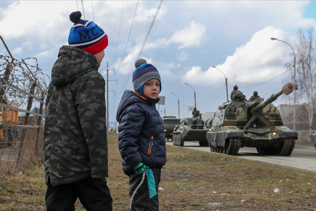 Boys watch Msta-S self-propelled howitzers passing by during a rehearsal of a military parade to be held on May 9 and mark the 75th anniversary of the victory in World War II in Yekaterinburg, Russia on April 14, 2020. (Photo by Donat Sorokin/TASS)