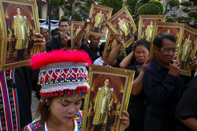 Mourners hold up pictures of Thailand's late King Bhumibol Adulayadej as they wait in line to enter the Throne Hall at the Grand Palace for the first time to pay respects to his body that is kept in a golden urn in Bangkok, Thailand, October 29, 2016. (Photo by Athit Perawongmetha/Reuters)