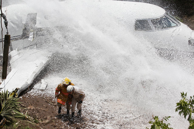 Firefighters take cover from firefighting foam applied onto the wreckage of a Gulfstream G200 aircraft that skidded off the runway during landing at Toncontin International Airport in Tegucigalpa, Honduras on May 22, 2018. (Photo by Jorge Cabrera/Reuters)