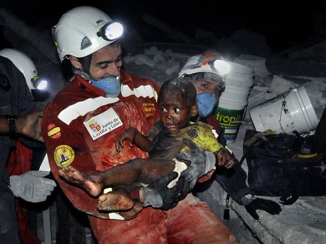 """In this January 2010 photo submitted by the Washington Post tilted  """"Rescue"""", a tiny baby named Reggie Claude is rescued from the rubble of his home. Disaster relief workers and family members rejoiced as Oscar Vega carried the child through the streets. (Photo by Carol Guzy/AP Photo/The Washington Post)"""