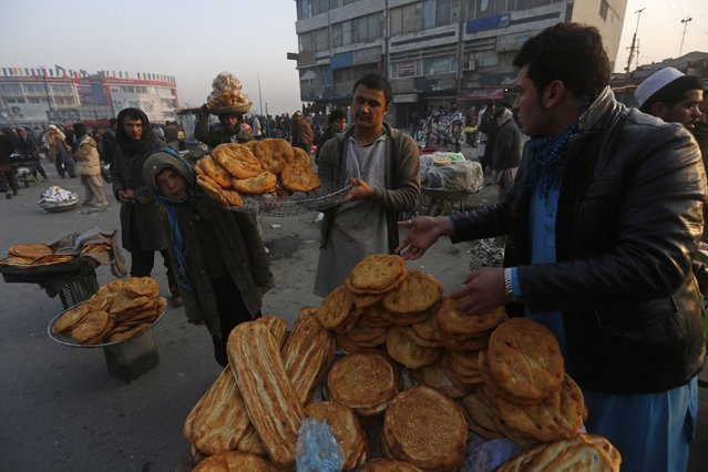Afghan men place bread for sale at a market during the early morning hours in Kabul, January 11, 2015. (Photo by Omar Sobhani/Reuters)