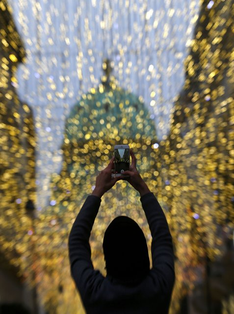 A woman takes photographs of Christmas illumination in central Vienna, Austria, December 9, 2015. (Photo by Heinz-Peter Bader/Reuters)
