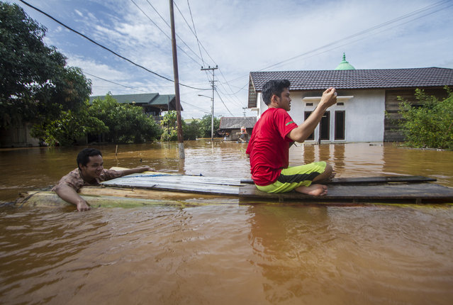 People use a makeshift raft to cross through a flooded village in Banjar, South Kalimantan on Borneo Island, Indonesia, in this Saturday, January 16, 2021 photo. Many thousands of people have been evacuated and a number have been killed in recent days in flooding on Indonesia's Borneo island, officials said Sunday. (Photo by Putra/AP Photo)