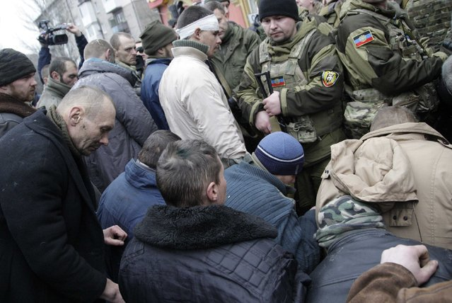 Prisoners of war (POWs), representing Ukrainian armed forces and escorted by members of the armed forces of the separatist self-proclaimed Donetsk People's Republic, kneel down on the ground as they visit a public transport stop, where civilians were earlier killed on Thursday, in Donetsk, January 22, 2015. (Photo by Alexander Ermochenko/Reuters)