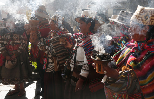 "Andean religious leaders carry urns with burning incense in a procession of the Bolivian deity statuette ""illa of Ekeko"" as it is driven to the Alasitas Fair, in which Ekeko is the central figure, in La Paz, Bolivia, Saturday, January 24, 2015. (Photo by Juan Karita/AP Photo)"