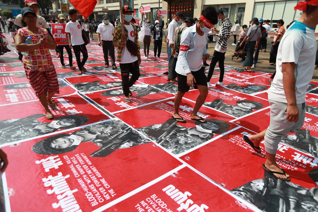 """Anti-coup protesters step on posters with an image of a soldier and a Burmese sign that reads """"armed terrorist"""" plastered on a road in Yangon, Myanmar Monday, February 22, 2021. Protesters gathered in Myanmar's biggest city Monday despite the ruling junta's thinly veiled threat to use lethal force if people answered a call for a general strike opposing the military takeover three weeks ago. (Photo by AP Photo/Stringer)"""