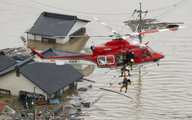 An aerial view shows a local resident being rescued from a submerged house by rescue workers using helicopter at a flooded area in Kurashiki, southern Japan, in this photo taken by Kyodo July 7, 2018. (Photo by Kyodo News via Reuters)