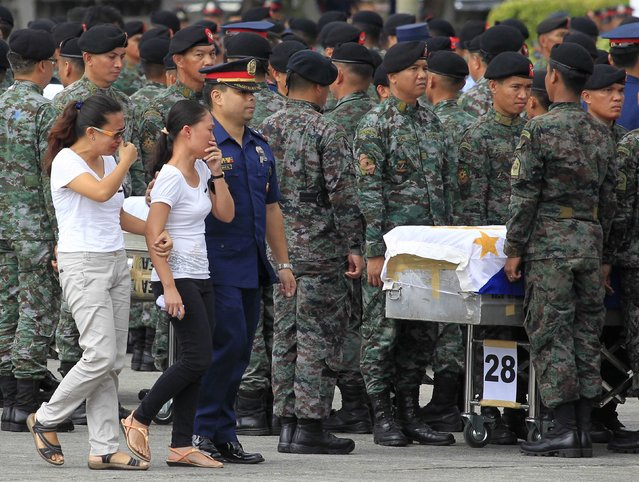 Women react as they view a metal casket containing the body of their relative, who was one of the Special Action Force (SAF) police killed in Sunday's clash with Muslim rebels, at Villamor Air Base in Pasay city, metro Manila January 29, 2015. (Photo by Romeo Ranoco/Reuters)