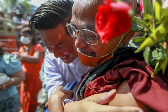 A released prisoner hugs a Buddhist monk outside the Insein prison in Yangon, Myanmar Friday, February 12, 2021. (Photo by AP Photo/Stringer)