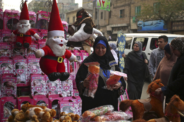 A woman looks at a doll as she stands next to Santa Claus themed Christmas items at a street market in Cairo, Egypt, December 21, 2015. (Photo by Asmaa Waguih/Reuters)