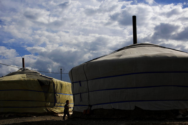 A boy stands next to a ger, a traditional Mongolian tent, in an area known as a ger district in Ulan Bator June 22, 2013. Approximately 60 percent of the population of Ulan Bator live in settlements known as ger districts and in many cases residents have limited access to basic services such as water and sanitation. According to a 2010 National Population Center census, every year between thirty and forty thousand people migrate from the countryside to the capital Ulan Bator. Ger districts in the city have been expanding rapidly in recent years. Mongolia is the world's least densely populated country, with 2.8 million people spread across an area around three times the size of France. (Photo by Carlos Barria/Reuters)
