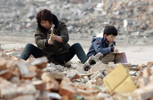 Primary school student Lele (R), 7, does his homework as his grandmother smashes concrete to look for recyclable steel bars at a demolition site in Zhengzhou, Henan province February 3, 2015. Lele's father was diagnosed with Leukemia four years ago and the family has been struggling to pay the medical bills. (Photo by Reuters/Stringer)