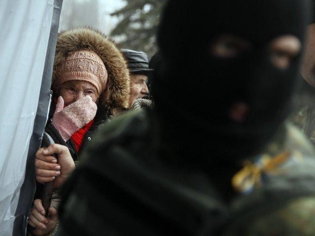 A woman cries as she waits for humanitarian aid near a Ukrainian serviceman stands nearby in Debaltseve, eastern Ukraine, February 6, 2015. (Photo by Gleb Garanich/Reuters)
