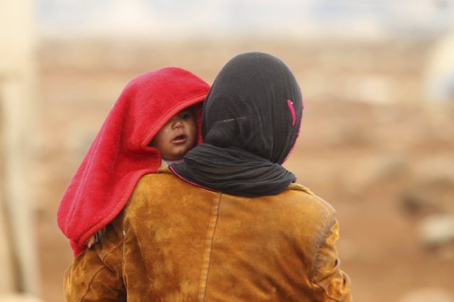 An Internally displaced Syrian woman carries a baby inside a refugee camp in the Hama countryside, Syria January 1, 2016. (Photo by Ammar Abdullah/Reuters)