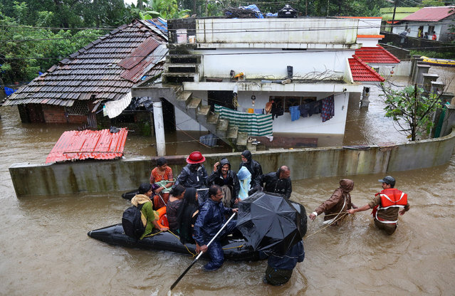 Rescue workers evacuate people from flooded areas after the opening of Idamalayar, Cheruthoni and Mullaperiyar dam shutters following heavy rains, on the outskirts of Kochi, India August 15, 2018. (Photo by Sivaram V/Reuters)