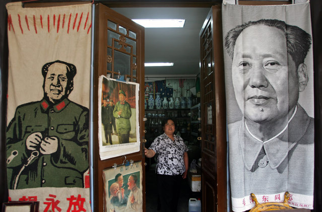 A shop vendor stands besides portraits of the late chairman Mao Zedong, on sale at a flea market in Beijing, May 16, 2006. (Photo by Jason Lee/Reuters)