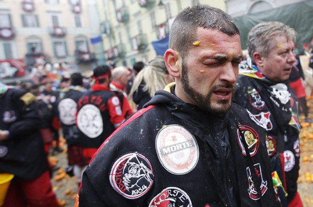 A member of a rival team gestures after being hit in one eye during an annual carnival battle with oranges in the northern Italian town of Ivrea February 15, 2015. (Photo by Max Rossi/Reuters)