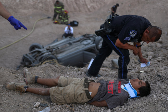 A policeman from the city of La Joya stands over an 18-year-old male who lies injured after crashing his vehicle while transporting two men and a woman who illegally crossed the U.S. border from Mexico in Penitas, Texas on August 31, 2018. (Photo by Adrees Latif/Reuters)