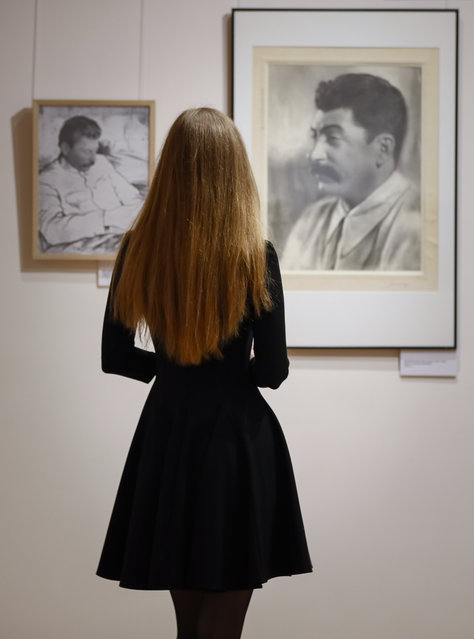 """A visitor looks at portraits of Soviet leader Joseph Stalin by Soviet photographer Moses Nappelbaum during a press preview of the exhibition """"Known and Unknown Nappelbaum"""" in Moscow, Russia 02 April 2021. More than 230 works created by Nappelbaum in different periods are presented in the exhibition based on the Nappelbaum family archive. (Photo by Yuri Kochetkov/EPA/EFE)"""