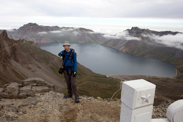 In this Saturday, August 18,2018, photo, Tarjei Naess Skrede of Norway who is hiking with Roger Shepherd of Hike Korea stands near a view of the caldera and Lake Chon on Mount Paektu in North Korea. (Photo by Ng Han Guan/AP Photo)