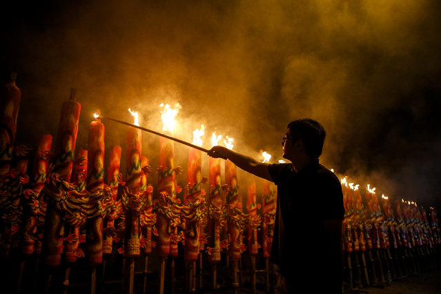 A Malaysian Chinese ethnic man lights a giant joss stick on the eve of the Chinese Lunar New Year celebrations at a temple in Kajang, outside Kuala Lumpur, Malaysia, late February 18, 2015. (Photo by Azhar Rahim/EPA)