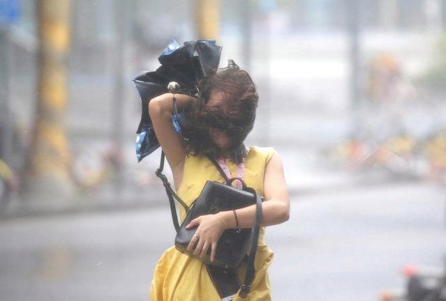 A woman is battered by the wind under Typhoon Mangkhut attack in Hong Kong, China September 16, 2018. (Photo by Bobby Yip/Reuters)