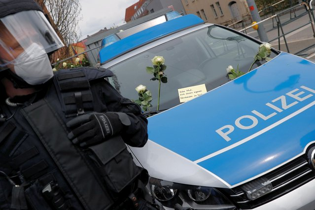 """A police officer wearing a patch reading, """"vaccinated"""", stands guard next to a car with a card on it during a protest against the government measures to curb the spread of the coronavirus disease (COVID-19) in Weimar, Germany, May 1, 2021. The card reads, """"be brave to use your brain"""". (Photo by Kai Pfaffenbach/Reuters)"""