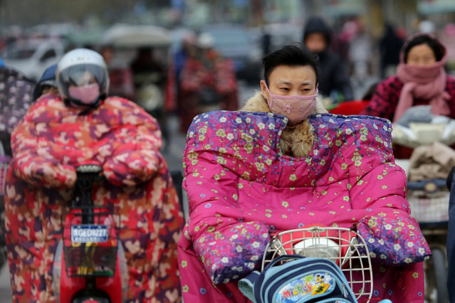 People wear special jackets made for riders to keep out the wind during a cold day in Lianyungang, Jiangsu province, November 23, 2016. (Photo by Reuters/Stringer)