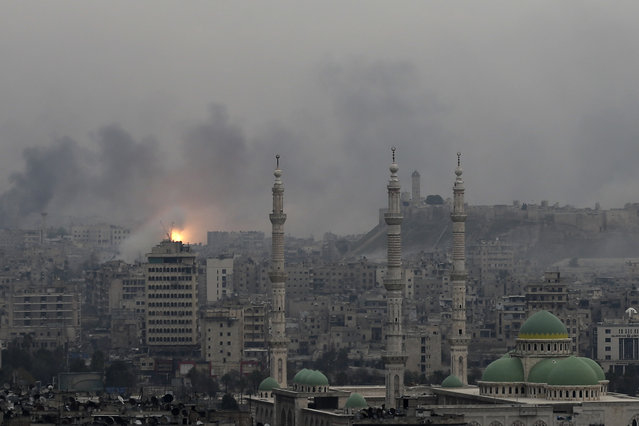 A ball of fire rises following a Syrian government air strike that hit rebel positions in the eastern neighborhoods of Aleppo, Syria, Monday, December 5, 2016. The government seized large swaths of the Aleppo enclave under rebel control since 2012 in the offensive that began last week. The fighting was most intense Monday near the dividing line between east and west Aleppo as government and allied troops push their way from the eastern flank, reaching within less than a kilometer (half a mile) from the citadel that anchors the center of the city. (Photo by Hassan Ammar/AP Photo)