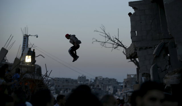 A Palestinian youth practices his Parkour skills over the ruins of houses, that witnesses said were destroyed during a 50-day war last summer in the Shejaia neighborhood east of Gaza City, May 12, 2015. (Photo by Mohammed Salem/Reuters)
