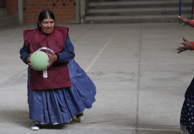 """In this January 28, 2105 photo, Rosa Lima plays handball with other elderly Aymara indigenous women in El Alto, Bolivia. """"There are days my knees hurt from rheumatism, but when I play it goes away"""", said 77-year-old Lima, who first began doing simple exercises eight years ago, then later took up team handball. She lives alone and looks forward to playing with her friends every week. (Photo by Juan Karita/AP Photo)"""