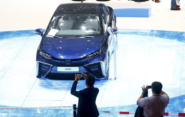 People take pictures of Toyota Mirai car ahead of the 85th International Motor Show in Geneva, March 2, 2015.             REUTERS/Arnd Wiegmann (SWITZERLAND  - Tags: TRANSPORT BUSINESS)