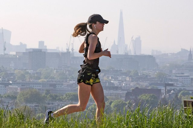 A jogger is seen running at Hampstead Heath with London in the background on June 1, 2021. (Photo by Joshua Bratt/London News Pictures)