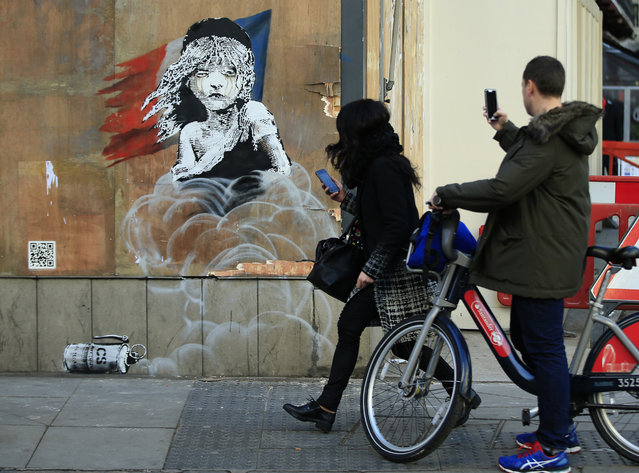 Commuters take photos on their phones of a new artwork by British artist Banksy opposite the French Embassy, in London, Monday, January 25, 2016. The artwork depicts the young girl from the musical Les Miserables with tears streaming from her eyes as a can of CS gas lies beneath her. The work is criticising the use of teargas in the refugee camp in Calais. (Photo by Alastair Grant/AP Photo)