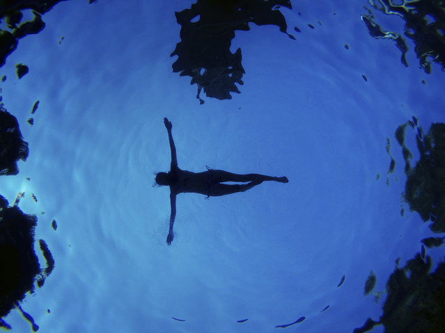 In this underwater picture a woman floats in a swimming pool during a summer day in Madrid, Spain, August 28, 2016. (Photo by Daniel Ochoa de Olza/AP Photo)