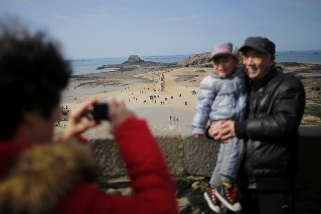 A family poses for a souvenir picture during a record low tide in Saint Malo, western France, March 21, 2015. (Photo by Stephane Mahe/Reuters)