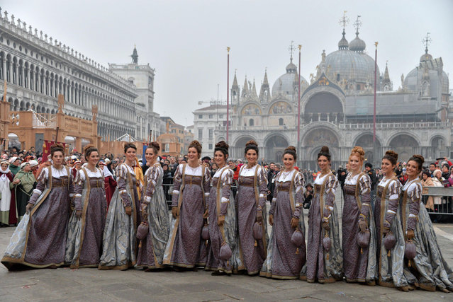 """The """"parade of the Maries"""" crosses St. Mark's Square on the occasion of the Venice Carnival, in Venice, Italy, Saturday, January 30, 2016. People attended the Venice Carnival, celebrated Saturday under heightened security following the sexual assaults on New Year's Eve in Cologne and the ongoing terror threat in Europe. Authorities have increased surveillance throughout the city, including the number of officers on patrol, both under-cover and in uniform. (Photo by Andrea Merola/ANSA via AP Photo)"""