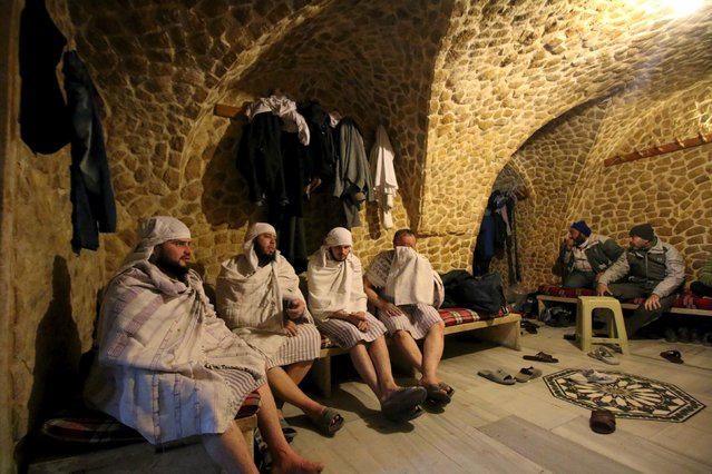 Customers rest after taking a steam bath at al-Salhiyeh traditional hammam, at a rebel-controlled area in the old city of Aleppo, Syria January 26, 2016. Al-Salhiyeh traditional hammam reopened its door after four years of closure. Picture taken January 26, 2016. (Photo by Abdalrhman Ismail/Reuters)