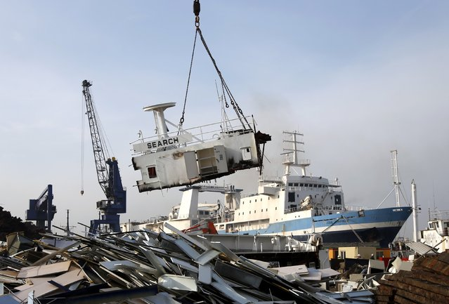 A crane lifts a large block cut from of a French seismic vessel at the Galloo ship recycling plant in Ghent March 24, 2015. (Photo by Francois Lenoir/Reuters)